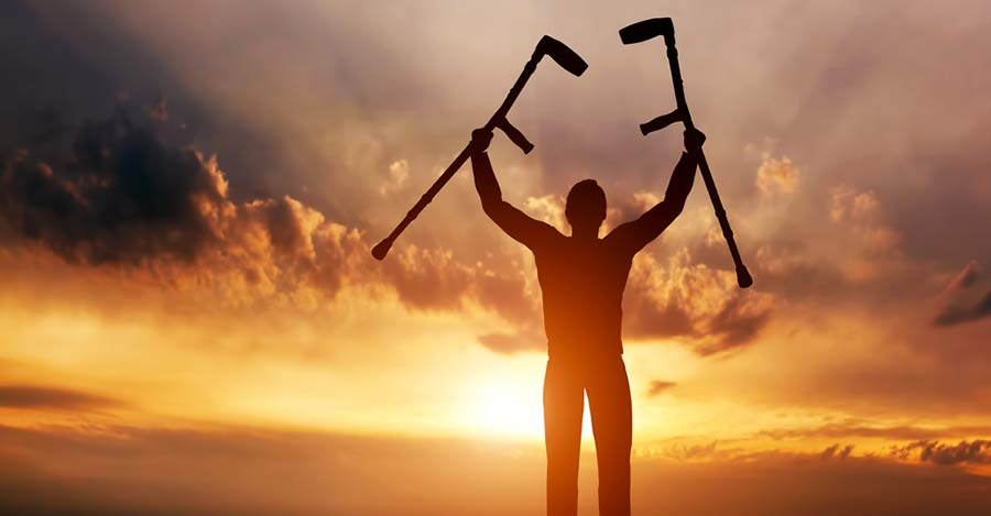 worldcrutches-Man-with-crutches-raised-in-both-hands-at-sunset